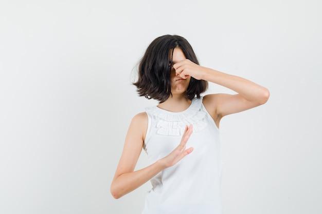 Mała dziewczynka szczypie nos z powodu nieprzyjemnego zapachu w białej bluzce i wygląda na zniesmaczoną, widok z przodu.