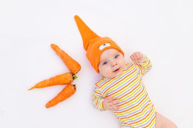 Mała dziewczynka sześć miesięcy leżącego na białym tle z marchewką