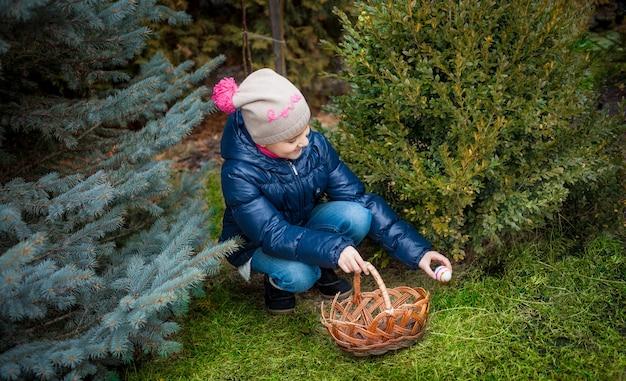 Mała dziewczynka szuka jajek na wielkanoc na podwórku