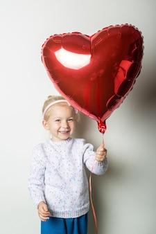 Mała dziewczynka trzyma balon serce na jasnym tle. koncepcja na walentynki, urodziny. transparent.
