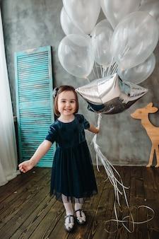 Mała dziewczynka trzyma balony w pokoju