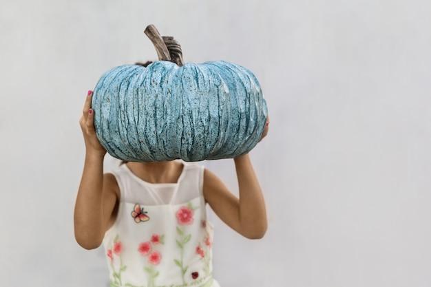 Mała dziewczynka trzyma błękitnej dyni przed jej twarzą