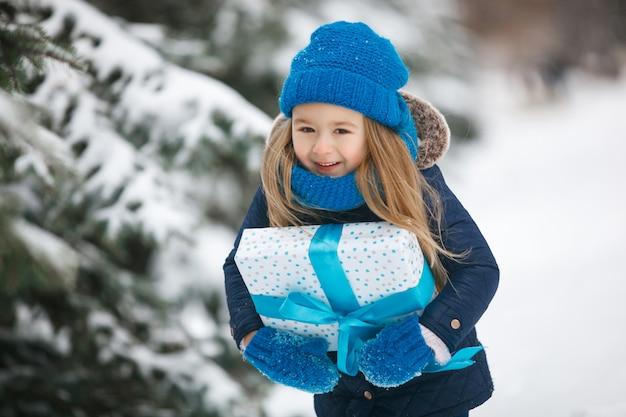 Mała dziewczynka trzyma boże narodzenie prezent w jej rękach i emocjonalnie ono uśmiecha się. dziecko ma na sobie niebieski czapka, rękawiczki, rękawiczki, szalik