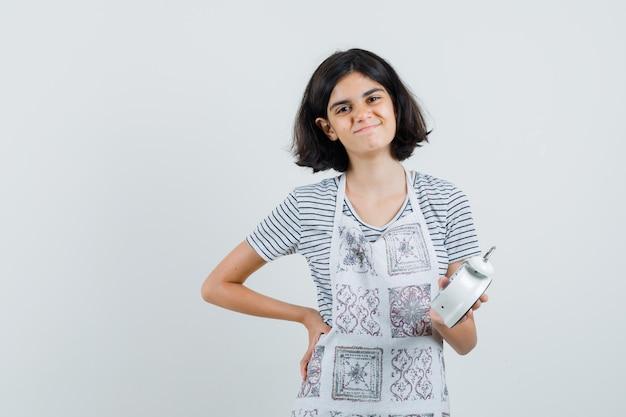 Mała dziewczynka trzyma budzik w koszulce, fartuchu i wygląda wesoło