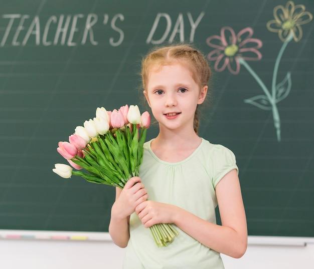 Mała dziewczynka trzyma bukiet kwiatów