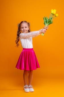 Mała dziewczynka trzyma bukiet żółtych tulipanów na żółtym tle