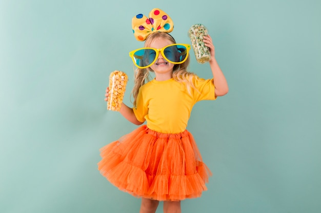Mała dziewczynka trzyma cukierki podczas noszenia dużych okularów przeciwsłonecznych