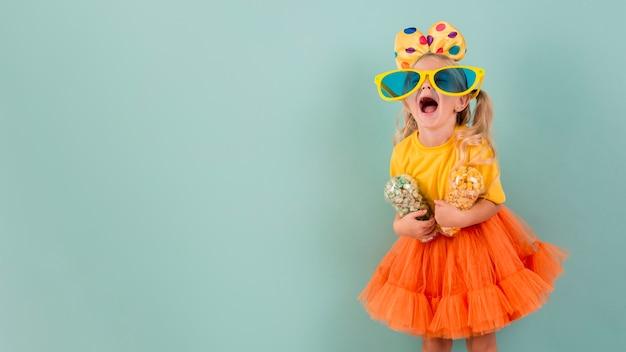 Mała dziewczynka trzyma cukierki z dużymi okularami przeciwsłonecznymi