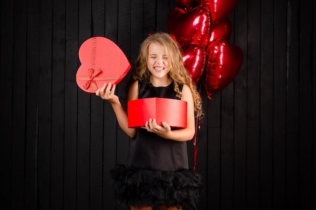 Mała dziewczynka trzyma czerwone pudełko w kształcie serca uśmiechnięte na czarnym tle.