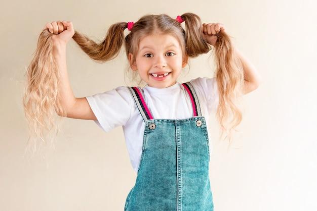 Mała dziewczynka trzyma długie włosy.