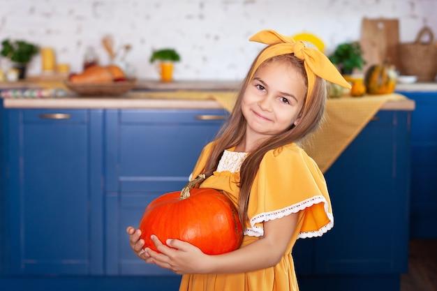 Mała dziewczynka trzyma dużą bani w kuchni w domu. żniwny. zdrowe odżywianie, wegetarianizm, witaminy, warzywa. słodkie dziecko przygotowuje się na halloween i zabawy z dyniami w kuchni