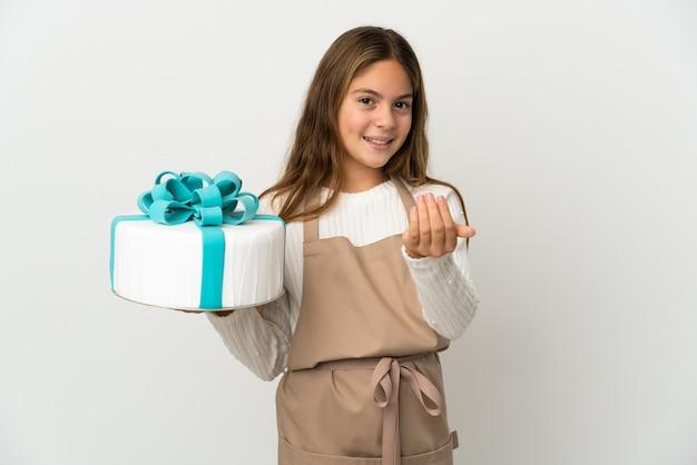 Mała dziewczynka trzyma duży tort na białym tle, zapraszając do przyjścia z ręką. cieszę się, że przyszedłeś