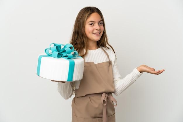 Mała dziewczynka trzyma duży tort na odizolowanej białej ścianie wyciągając ręce na bok, by zaprosić do przyjścia