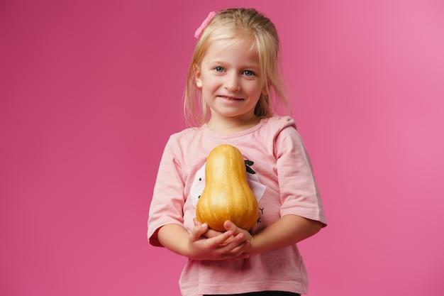 Mała dziewczynka trzyma dyni w dłoniach