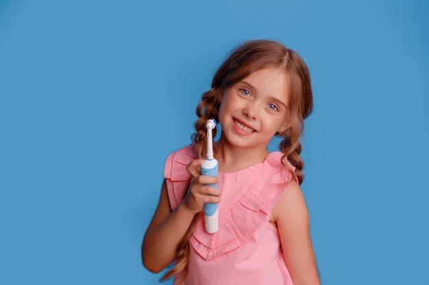 Mała dziewczynka trzyma elektryczną szczoteczkę do zębów