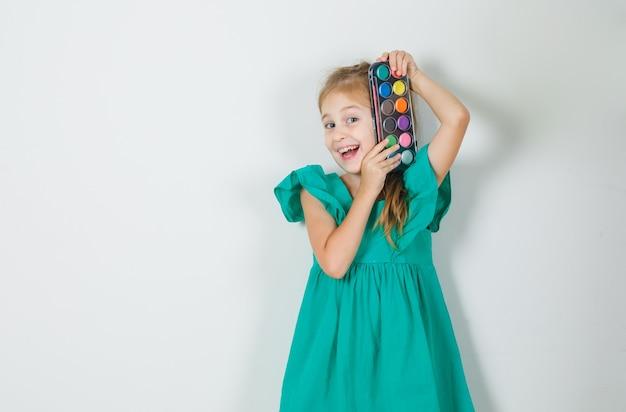 Mała dziewczynka trzyma farby akwarelowe z pędzelkiem w zielonej sukience i wygląda wesoło