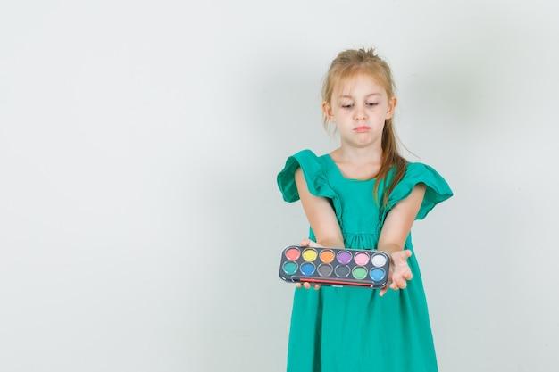 Mała dziewczynka trzyma farby akwarelowe z pędzlem w zielonej sukience i wygląda poważnie