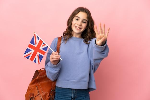 Mała dziewczynka trzyma flagę zjednoczonego królestwa na białym tle na różowym tle szczęśliwa i liczy cztery palcami