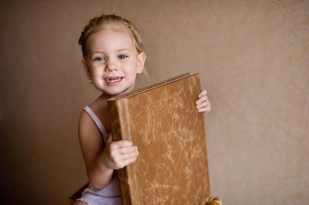 Mała dziewczynka trzyma fotoksiążkę w naturalnej brązowej skórze.