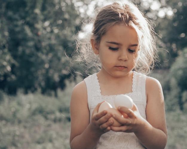 Mała dziewczynka trzyma i zbiera jaja dobrej jakości, ekologiczne i zwracające uwagę na farmę.