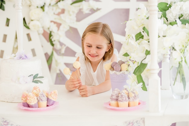 Mała dziewczynka trzyma kolorowych słodkich lizaków w cukierku barze