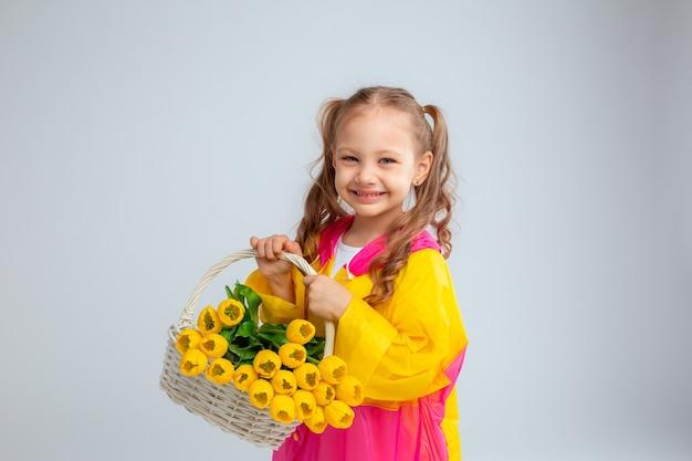 Mała dziewczynka trzyma kosz kwiatów