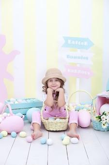 Mała dziewczynka trzyma kosz z wielkanocnymi wielobarwnymi jajkami.