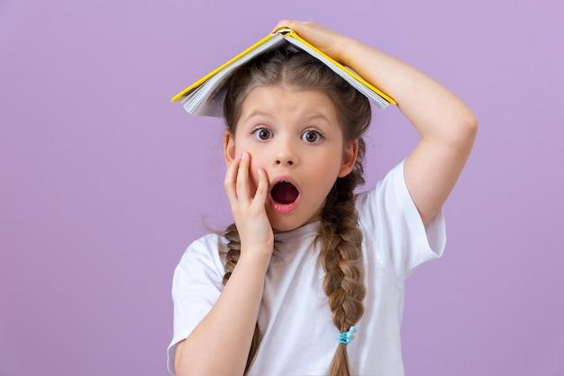 Mała dziewczynka trzyma książkę jak dach nad głową. bardzo zaskoczony.
