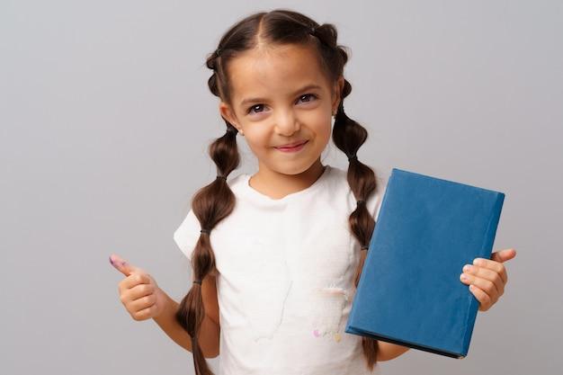 Mała dziewczynka trzyma książkę w ona ręki nad szarym tłem