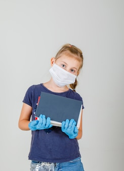 Mała dziewczynka trzyma książki i zeszyty w t-shirt, rękawiczki i widok z przodu maski medyczne.
