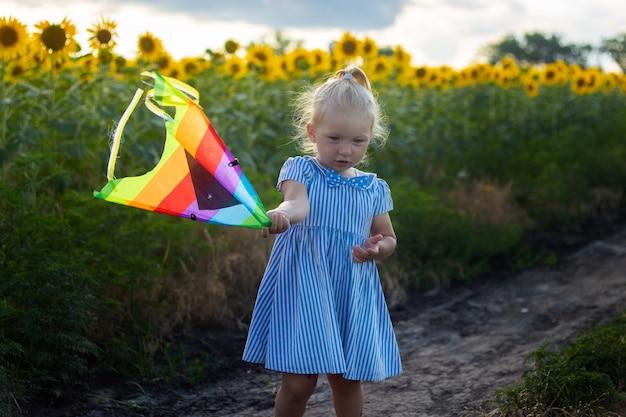 Mała dziewczynka trzyma latawiec na słonecznikowym polu.