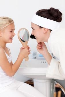 Mała dziewczynka trzyma lustro i macierzysty kładzenie makeup