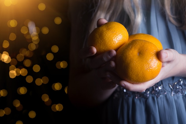 Mała dziewczynka trzyma mandarynki w dłoniach. przerwa świąteczna