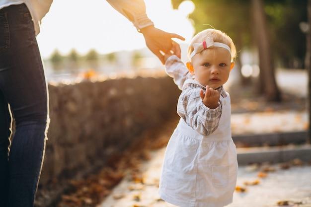 Mała dziewczynka trzyma matki rękę w parku