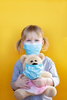 Mała dziewczynka trzyma misia zarówno w masce medycznej.