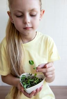 Mała dziewczynka trzyma miskę z microgreens w dłoniach. koncepcja zdrowego odżywiania