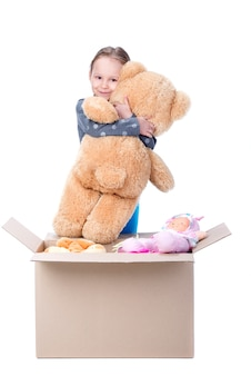 Mała dziewczynka trzyma niedźwiedzia w jej rękach i ono uśmiecha się.