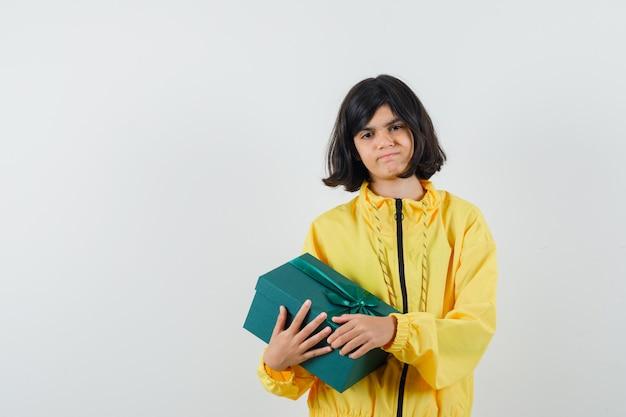 Mała dziewczynka trzyma obecne pudełko w żółtej bluzie z kapturem i wygląda na rozczarowaną, widok z przodu.