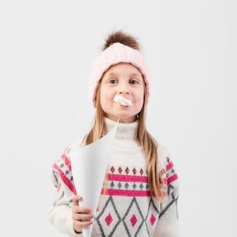 Mała dziewczynka trzyma papier i gumę do żucia