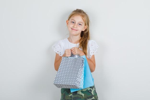 Mała dziewczynka trzyma papierowe torby w białej koszulce
