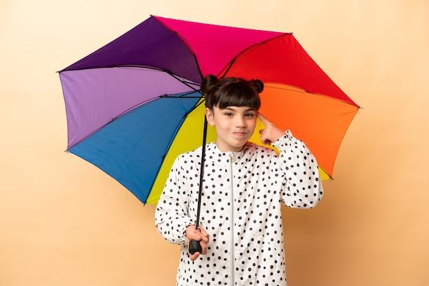 Mała dziewczynka trzyma parasol na białym tle