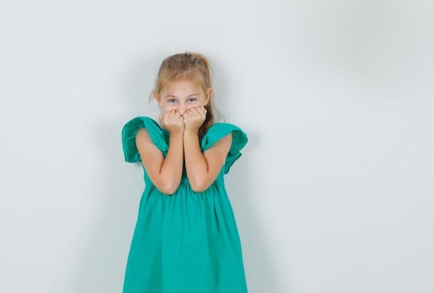 Mała dziewczynka trzyma pięści na twarzy w zielonej sukience i wygląda słodko