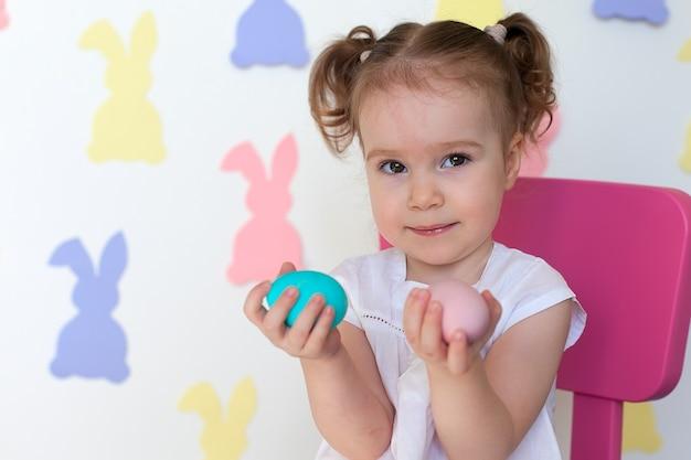 Mała dziewczynka trzyma pisanki z uśmiechem.