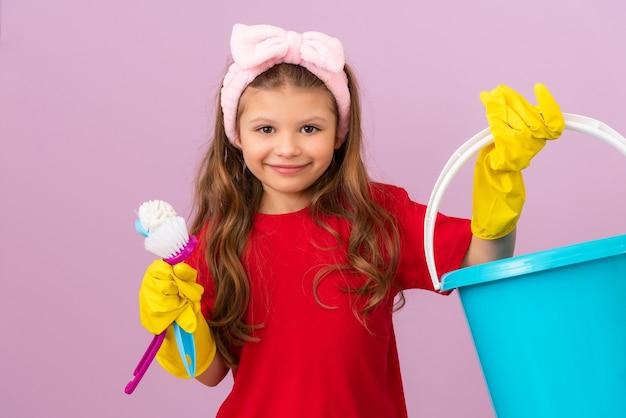 Mała Dziewczynka Trzyma Plastikowe Wiadro I Szczotki Do Sprzątania Pokoju. Premium Zdjęcia