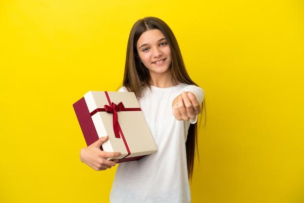Mała dziewczynka trzyma prezent na odosobnionym żółtym tle robienia pieniędzy gest