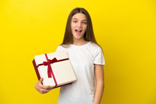Mała dziewczynka trzyma prezent na odosobnionym żółtym tle z niespodzianką wyrazem twarzy