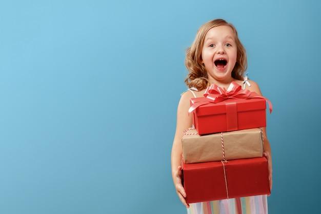 Mała dziewczynka trzyma pudełka z prezentami.