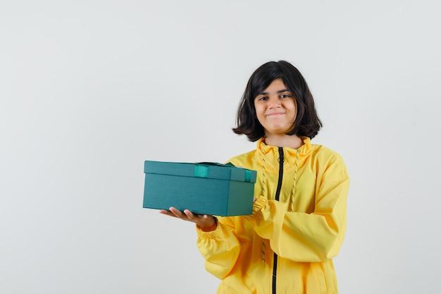 Mała dziewczynka trzyma pudełko w żółtej bluzie z kapturem i wygląda wesoło. przedni widok.