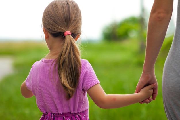 Mała dziewczynka trzyma rękę jej matki
