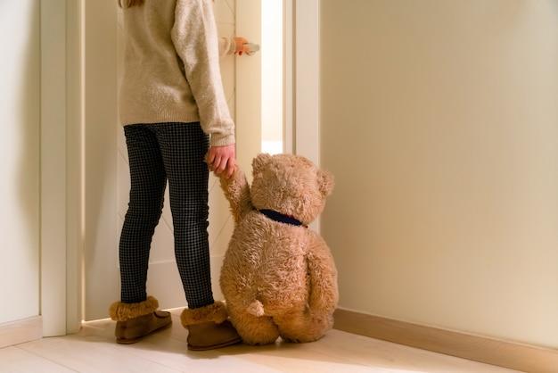 Mała dziewczynka trzyma rękę misia i idzie do swojego pokoju.